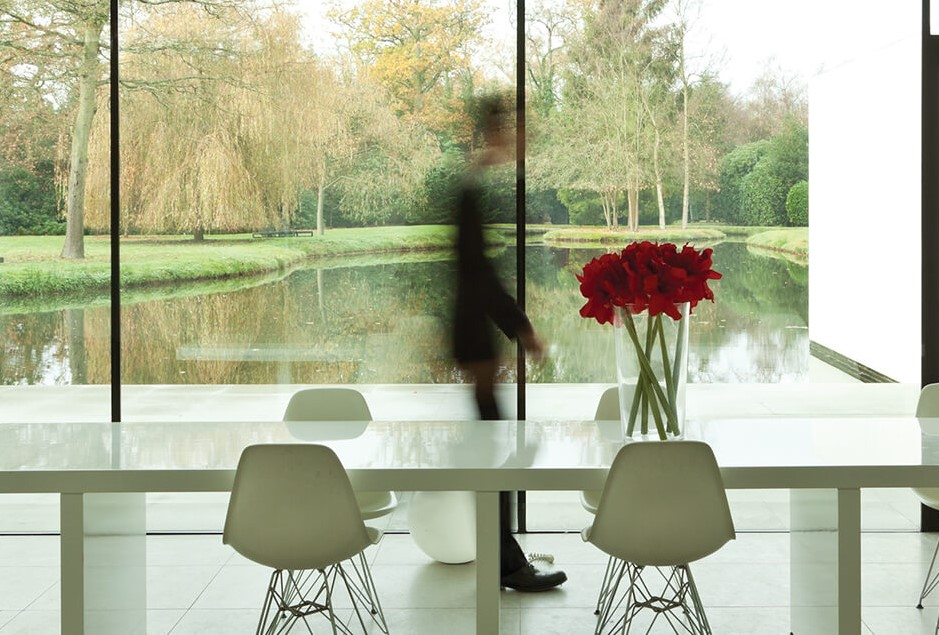 The Coutts Institute - man walks past table in glass room at speed