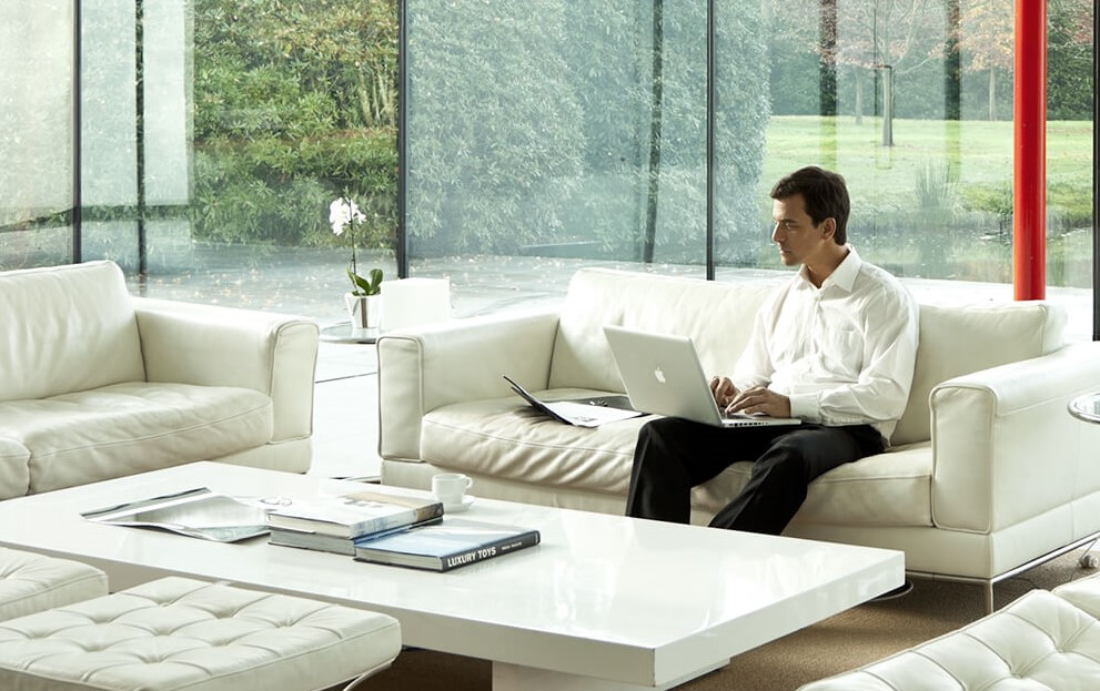 Wealth management - man sits on couch with laptop