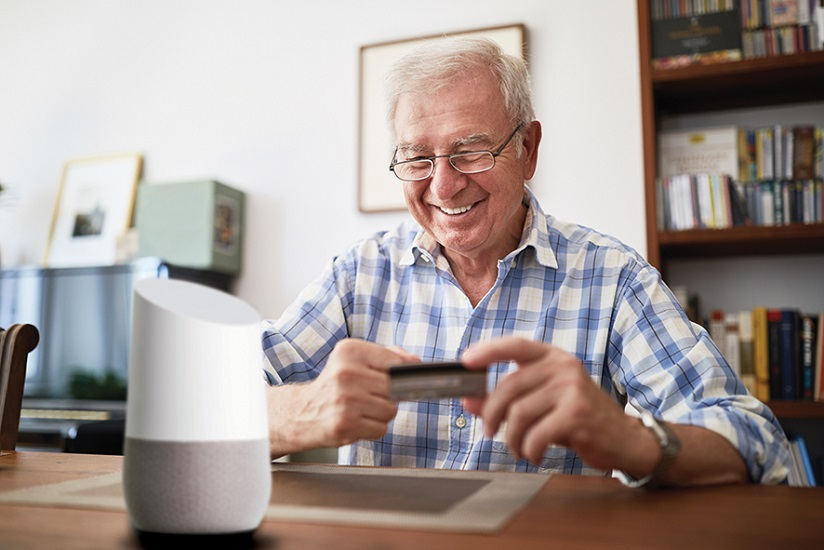 An older gentleman sits smiling with his credit card behind his voice activated device