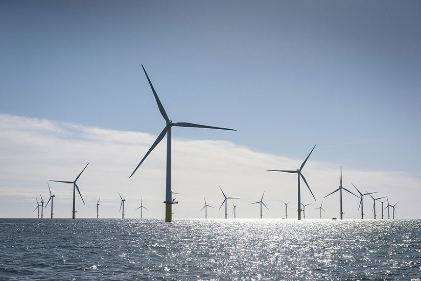 Wind turbines at sea, with sunlight shining off the water