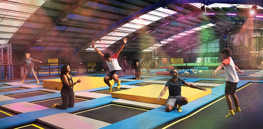 Children bounce on colourful trampolines, supervised by smiling adults