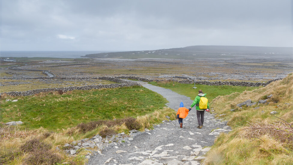 About us, strong, simple and fair, a man and boy safely walk a moorland path