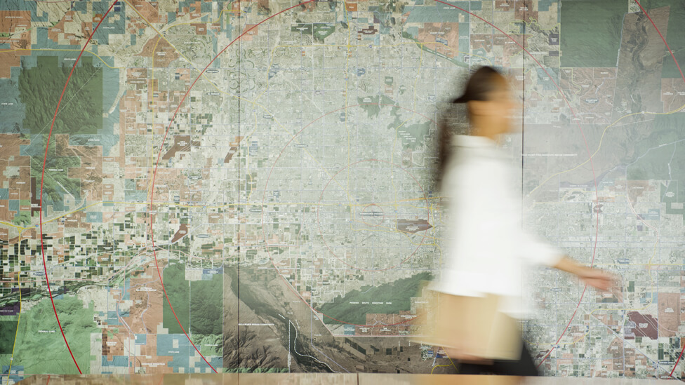 On the move, a lady is blurred-in-motion as she walks past a wallmap backdrop