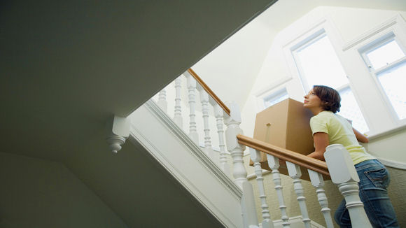 woman lifting box on stairs