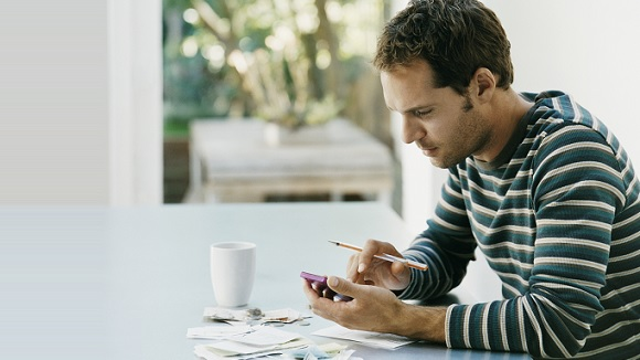 Man managing debt using mobile banking