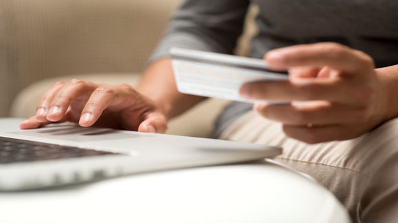 person typing bank card details on laptop