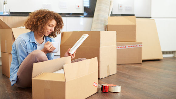 a young woman unpacking boxes in her new home after securing a mortgage