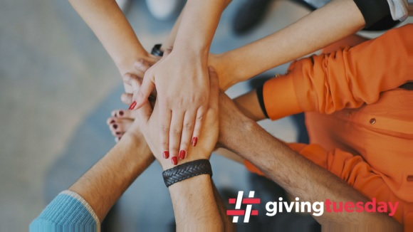Image of people putting their hands together for #givingtuesday