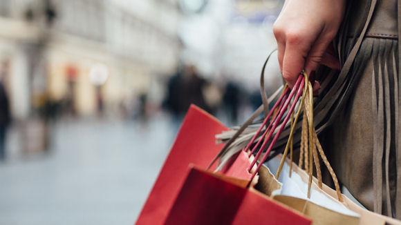 person holding shopping bags with high street in the background